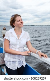 Attractive Caucasian woman with sunglasses in white shirt standing on ship deck