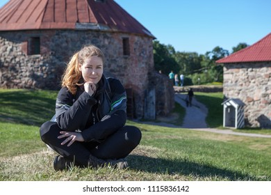 Attractive Caucasian woman wearing motorcycle outfit sitting on green meadow in some landmark attraction, copy space