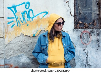 Attractive caucasian young woman, wearing yellow hoodie, blue denim jacket and sunglasses, posing in front of a white wall covered in blue graffiti and yellow paint, clash of modern and rustic