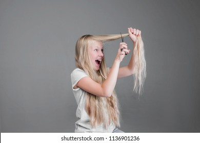 Attractive chaild girl  is cutting her long blond natural hair