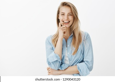 Attractive charismatic blond female student wear casual shirt laughing joyfully biting finger smiling satisfied winning place university exchange program, grinning happily against white background