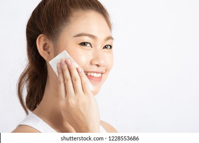 Attractive Charming Asian young woman smile and using tissue with toner for cleaning make up feeling so fresh and clean with healthy skin,isolated on white background,Beauty Cosmetics Concept