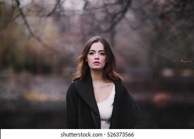 Attractive, charming young woman in a white cotton dress and dark coat walking in the autumn Park. Cloudy. Soft colors of nature. The melancholy mood.