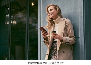 Attractive cheerful blond girl in trench coat with coffee to go happily using cellphone outdoor