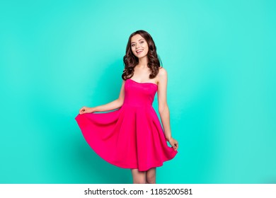 Attractive cheerful cute lovely groomed charming adorable caucasian wavy-haired girl in short fuchsia bright vivid dress, isolated over green turquoise teal pastel background
