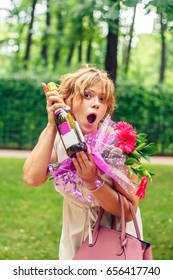 Attractive cheerful girl with a bottle of champagne near a green hedge.