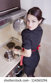 Attractive cheerful housewife in the kitchen