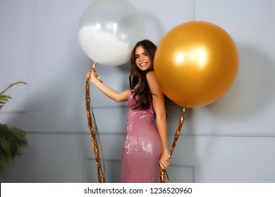 Attractive cheerful lady smiling in camera, posing for fashion magazine. Wearing long evening pink dress with sparkles and decollete. Two big balloons in her hands, having fun. Light grey background