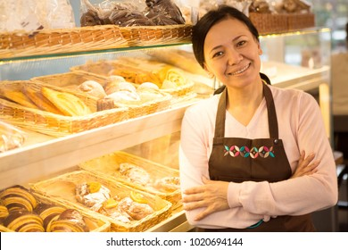 Attractive cheerful mature Asian female baker wearing an apron smiling joyfully to the camera posing at her bakery store copyspace small business owner entrepreneur cafe consumerism salesperson job.