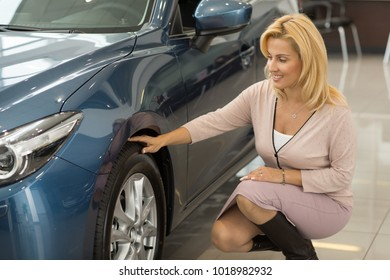 Attractive cheerful mature woman examining wheels and tires of a new automobile at the car dealership positivity driving maintenance buyer consumerism purchasing consumptions retail sales rental.
