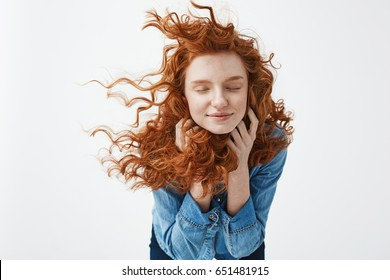 Attractive cheerful redhead girl with flying curly hair smiling laughing with closed eyes over white background.