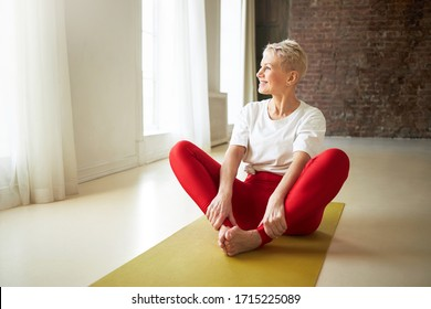 Attractive cheerful retired woman in sportswear sitting on yoga mat with knees bent, pressing soles of feet together doing baddha konasana. People, healthy lifestyle, activity and wellness concept