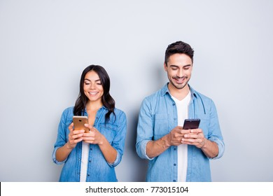 attractive, cheerful, smiling lovers in casual outfit, jeans shirts  having smart phones in hands, looking at screen, texting with each other, using 5g internet, standing over grey background