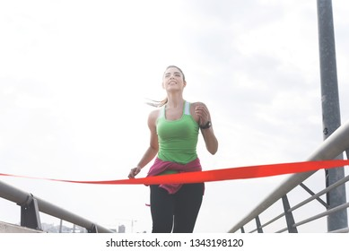 Attractive cheerful sporty young woman reaching the finish line of the race, Active lifestyle concept
