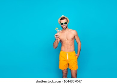 Attractive, cheerful, stunning, perfect, harsh, virile man in yellow shorts, having cocktail with small umbrella in hand and holding arm in pocket, isolated on blue background