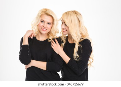 Attractive cheerful young blonde sisters twins talking and looking away over white background
