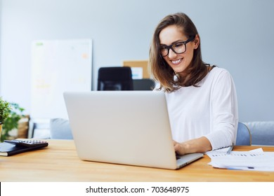 Attractive cheerful young businesswoman working on laptop and smiling while sitting at her desk in bright modern office