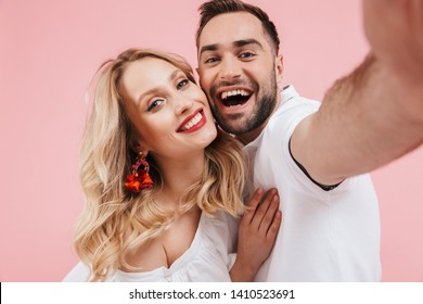 Attractive cheerful young couple in love standing together isolated over pink background, taking a selfie