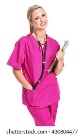 Attractive, cheerful, young female nurse wearing pink scrubs with a stethoscope around her neck and a clip under her arm.