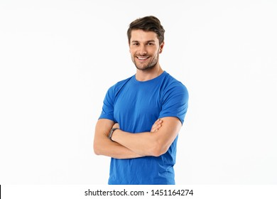 Attractive cheerful young fit sportsman wearing t-shirt standing isolated over white background, arms folded