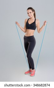 Attractive cheerful young sportswoman exercising with jumping rope over grey background