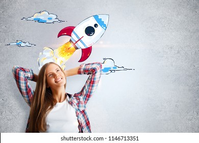 Attractive cheerful young woman daydreaming with creative launching rocket sketch on concrete wall background. Startup and success concept