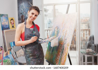 Attractive cheerful young woman enjoying painting at the art studio. Cheerful female artist drawing at workshop