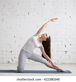 Attractive cheerful young woman working out indoors. Beautiful model doing exercises on blue mat in room with white walls. Side bend Parighasana, Gate Pose. Full length. Square image