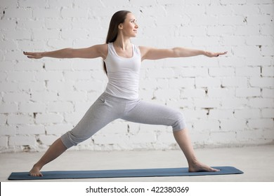 Attractive cheerful young woman working out indoors. Beautiful model doing exercises on blue mat in room with white walls. Warrior II posture, Virabhadrasana Two pose. Full length