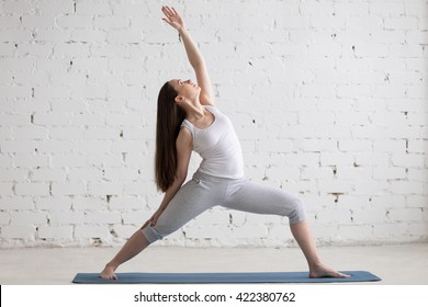 Attractive cheerful young woman working out indoors. Beautiful model doing exercises on blue mat in room with white walls. Peaceful or Reverse Warrior Pose, Viparita Virabhadrasana. Full length