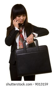 Attractive Chinese woman wearing a business attire holding a briefcase while talking on cell phone and checking wrist watch