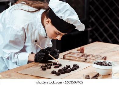 attractive chocolatier holding brush with gold powder near prepared chocolate candies