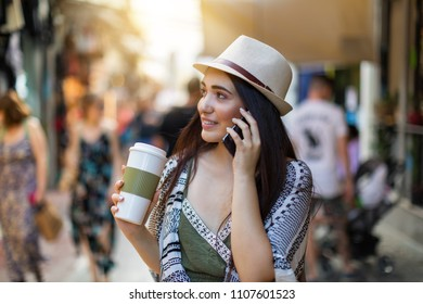 Attractive city hipster woman with a coffee in her hand walking in the street and talking to the mobile phone