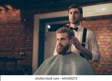 Attractive classy dressed barber shop hairdresser is turning client`s head to present his work for him. Stunning! Hairdo looks trendy and so perfect