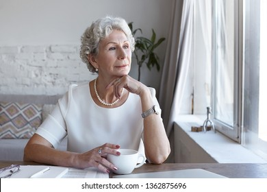 Attractive classy sixty year old mature woman wearing stylish wrist watch and pearl necklace spending nice time at home alone, sitting at her workplace with cup of coffee, looking through window