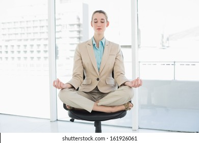 Attractive classy woman sitting in lotus position on her swivel chair with eyes closed