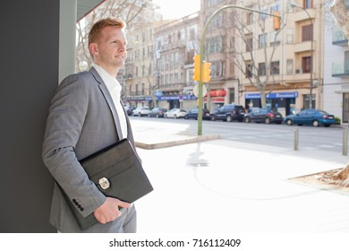 Attractive confident business man in financial city street with office building, carrying folder with paperwork, outdoors. Professional businessman, aspirational attitude, spacious sunny exterior.