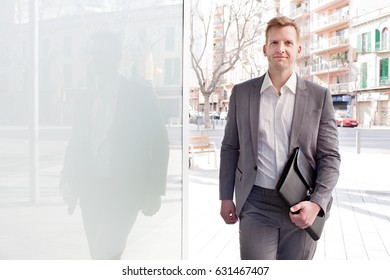 Attractive confident business man walking in financial city street, glass reflections in office building, carrying folder with paperwork, outdoors. Professional businessman on the go, sunny exterior.
