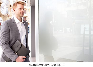 Attractive confident business man walking in financial city street with glass reflections in office building, carrying folder with paperwork, outdoors. Professional businessman on the go, exterior.