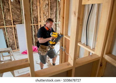 attractive and confident constructor carpenter or builder man working wood with electric drill at industrial construction site in installation and renovation work industry