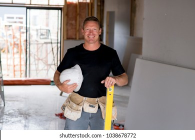 attractive and confident constructor carpenter or builder man with protective helmet posing happy working at industrial construction site in installation and renovation blue collar work industry