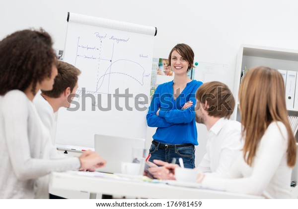 Attractive confident female in house corporate trainer giving a presentation to a group of businesspeople using a flipchart