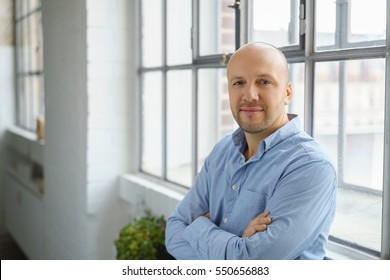 Attractive confident middle-aged man leaning against a windowsill in a relaxed position with folded arms staring thoughtfully at the camera, with copy space