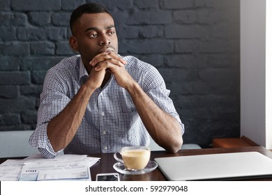 Attractive confident young African-American male entrepreneur having thoughtful and focused look, keeping hands clasped, thinking over strategy of his new project, waiting for partners at cafe