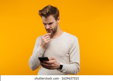 Attractive confused young man wearing pullower standing isolated over yellow background, using mobile phone