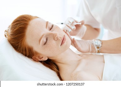 Attractive content red-haired caucasian woman receiving skin rejuvenation treatments in beauty salon. Face contouring procedure, revitalization.