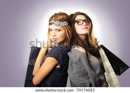 Attractive and cool looking teenage girls with headpieces holding shopping bags on gradient background