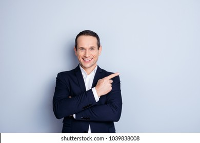 Attractive, corporate, positive, modern, fashionable man in formal wear with crossed hands pointing to copy space with forefinger, looking at camera, standing over gray background