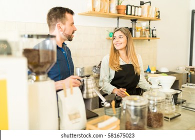Attractive couple of baristas talking and enjoying their work together in a coffee shop