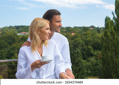 Una pareja atractiva en el albornoz disfrutando de las vistas desde la terraza de la habitación del hotel